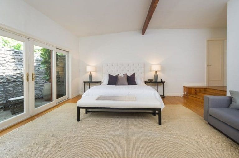 This master bedroom boasts a large rug covering the hardwood flooring. It has a gray couch on the side. The bed is lighted by two table lamps on the side tables.