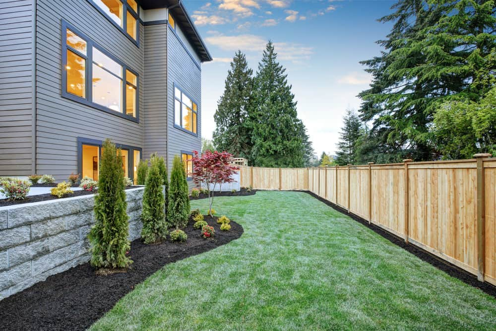 Backyard with wooden privacy fence around perimeter