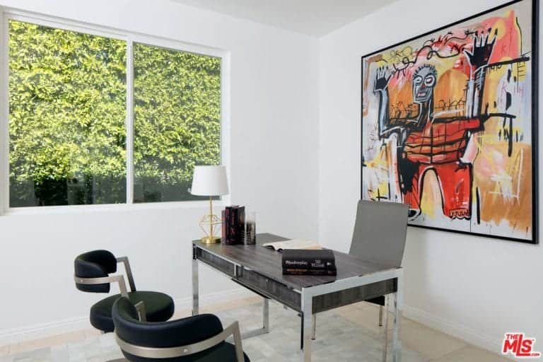 There is also a home office in the house boasting a clear glass window and an abstract painting wall design.