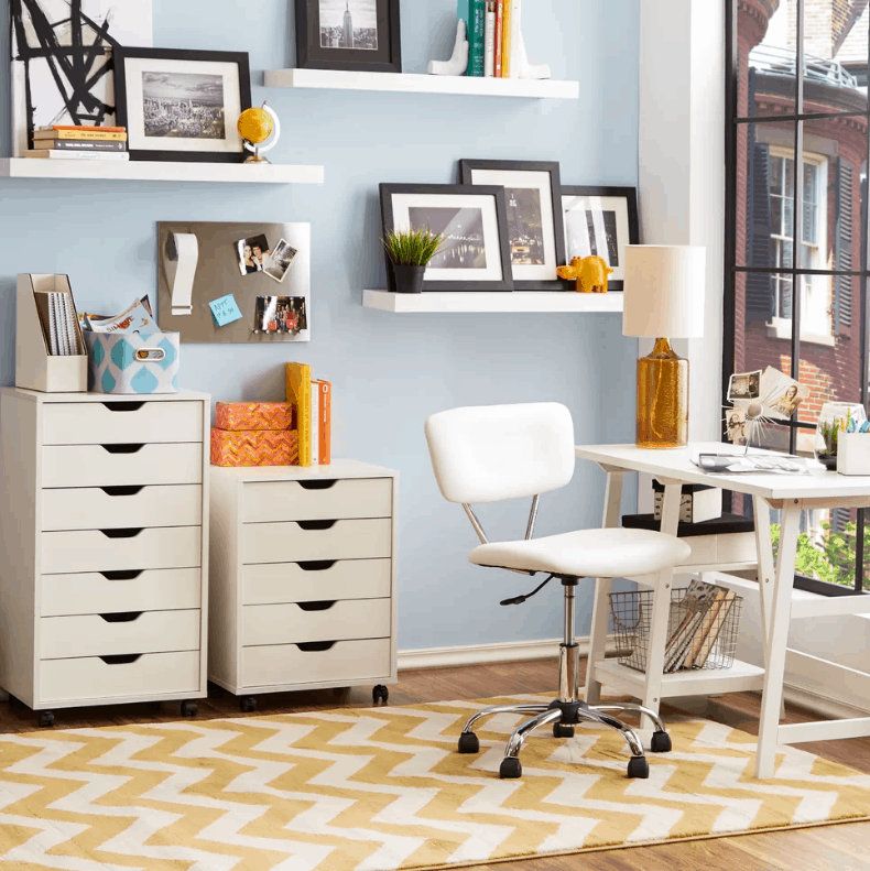 moder and contemporary home office with light blue walls and white built in shelves along with laminated flooring and yellow rug