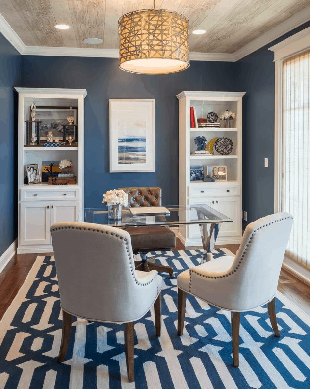 Traditional home office with blue walls and rug together with nice pendant lighting on a wooden regular ceiling.