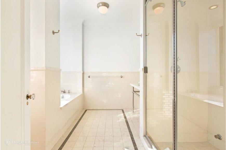 Master bathroom with a walk-in shower, a drop-in tub along with tiles flooring and wall lights.