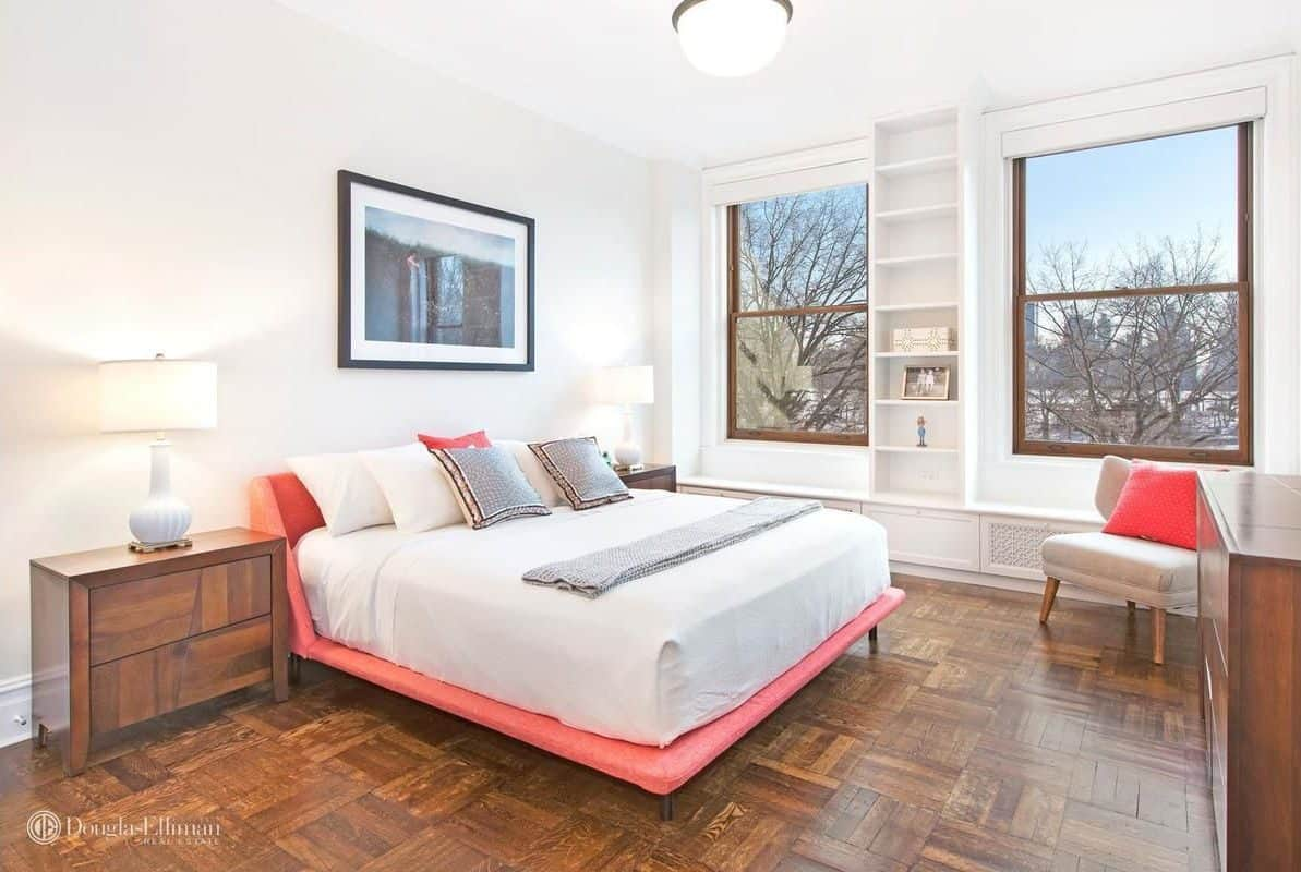 Primary bedroom with white walls and stylish hardwood flooring. There are two glass windows overlooking the beautiful surroundings.