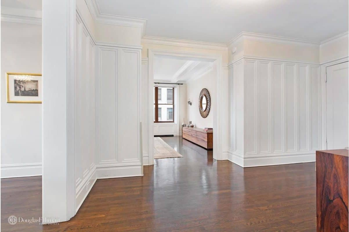 The hallway is wide and surrounded by white walls and hardwood flooring.