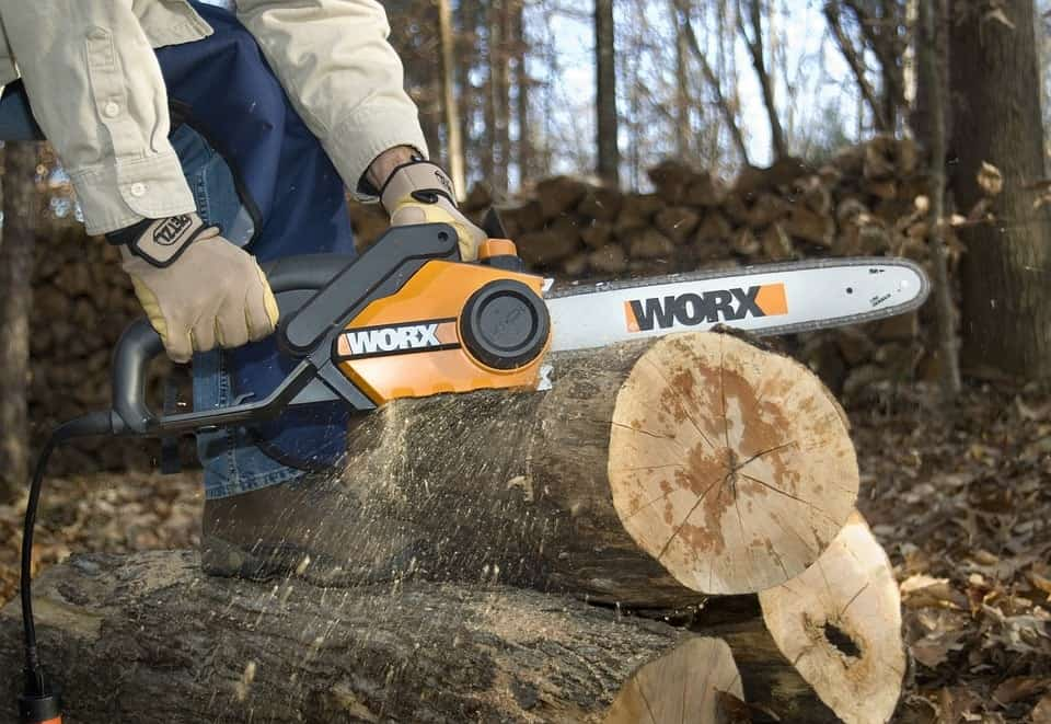 Cutting logs in the woods using an electric saw.