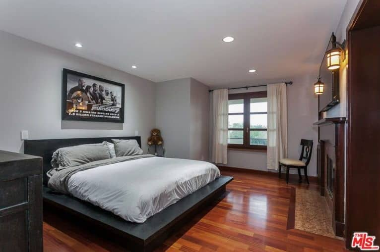 A large master bedroom with light gray walls and reddish hardwood floors. The room also features a sitting area and a study desk near the fireplace.