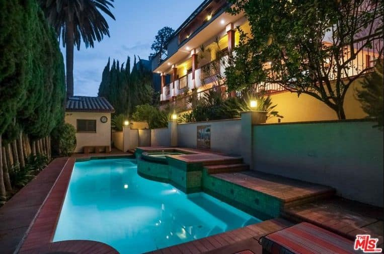 The house boasts a mediterranean-style pool under the L.A., surrounded by tall and mature trees.