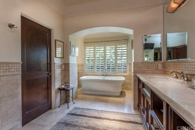 The bathroom features a freestanding tub on tiles flooring along with marble countertop sink.