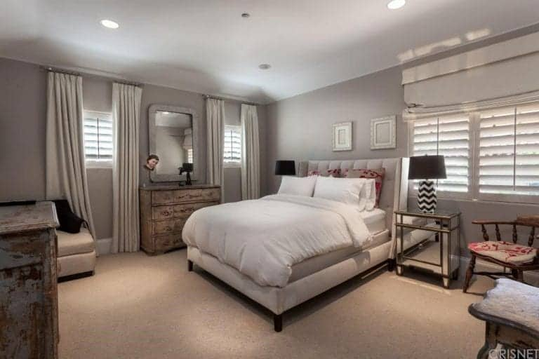 This master bedroom boasts gray walls and classy carpet flooring.