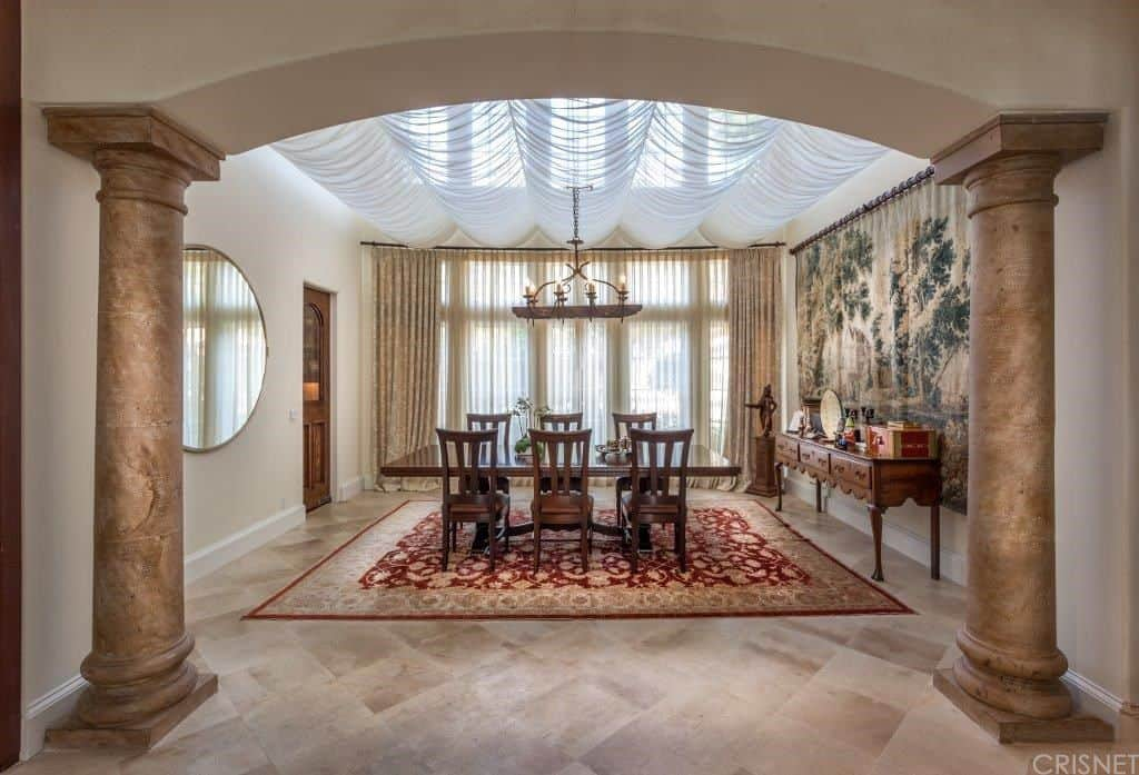Deluxe dining room lined with columns boasts a wooden dining set that sits on a red area rug. It has tiled flooring and floor to ceiling glass windows covered with sheer curtains.