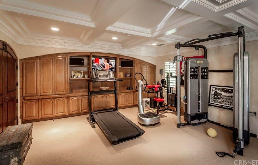 The Home Gym Looks Classy With Its Coffered Ceiling And Carpet Flooring  Together With A Wooden Cabinet And Shelving In Walnut Finish.