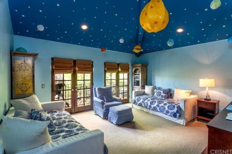 The room can be transitioned into a kids bedroom because of its outer space themed ceiling. The carpet flooring looks perfect with the light blue walls.