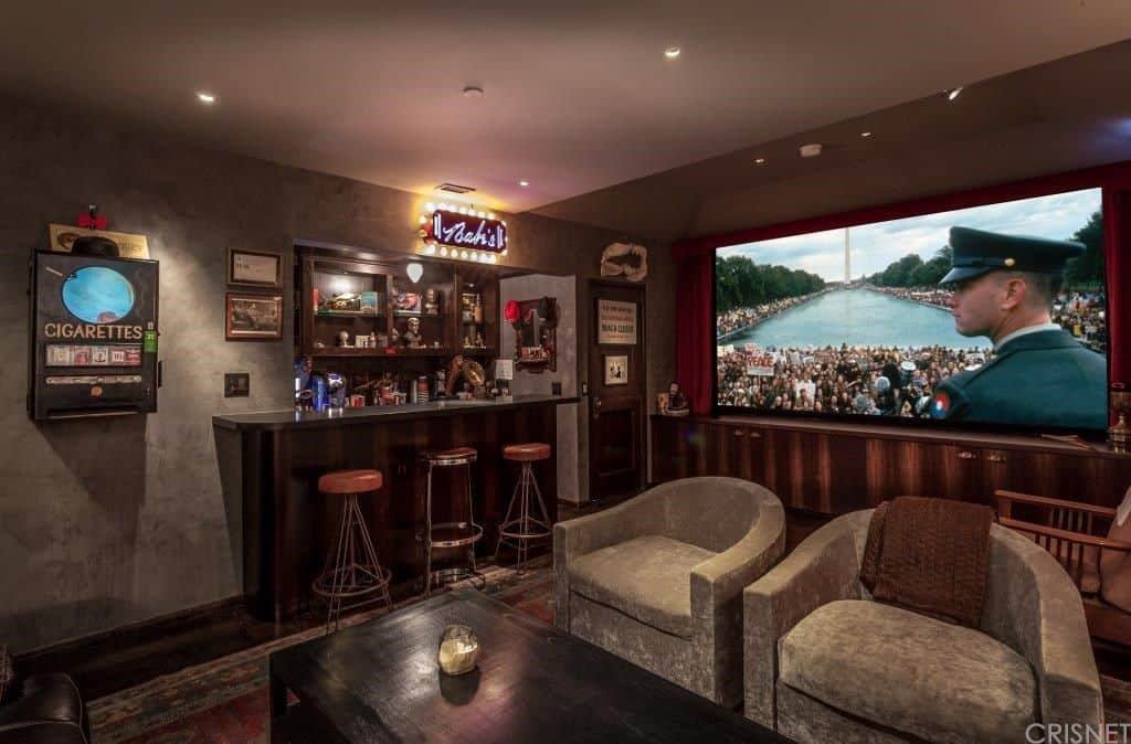 The quintessential man cave design with small bar, large wall-mounted flat screen TV, bar stools, neon bar sign and lounge area all darkly lit.
