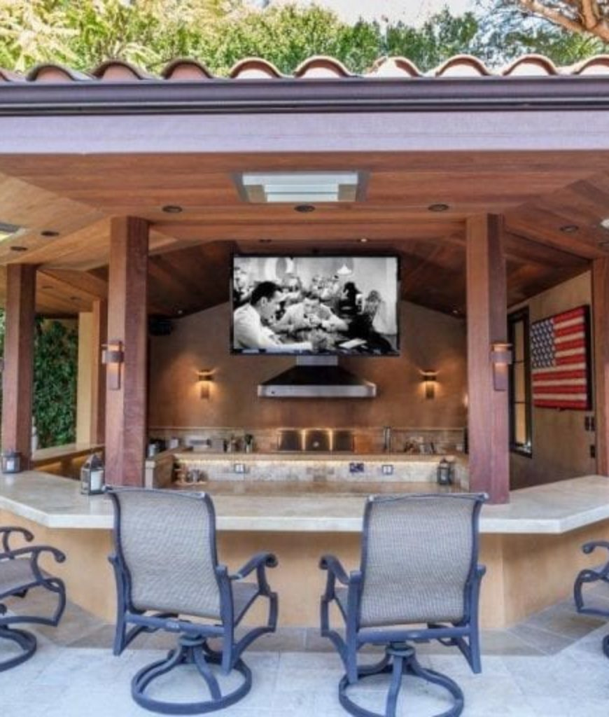 The outdoor kitchen has a hanging TV perfect for a weekend barbecue with family and friends.