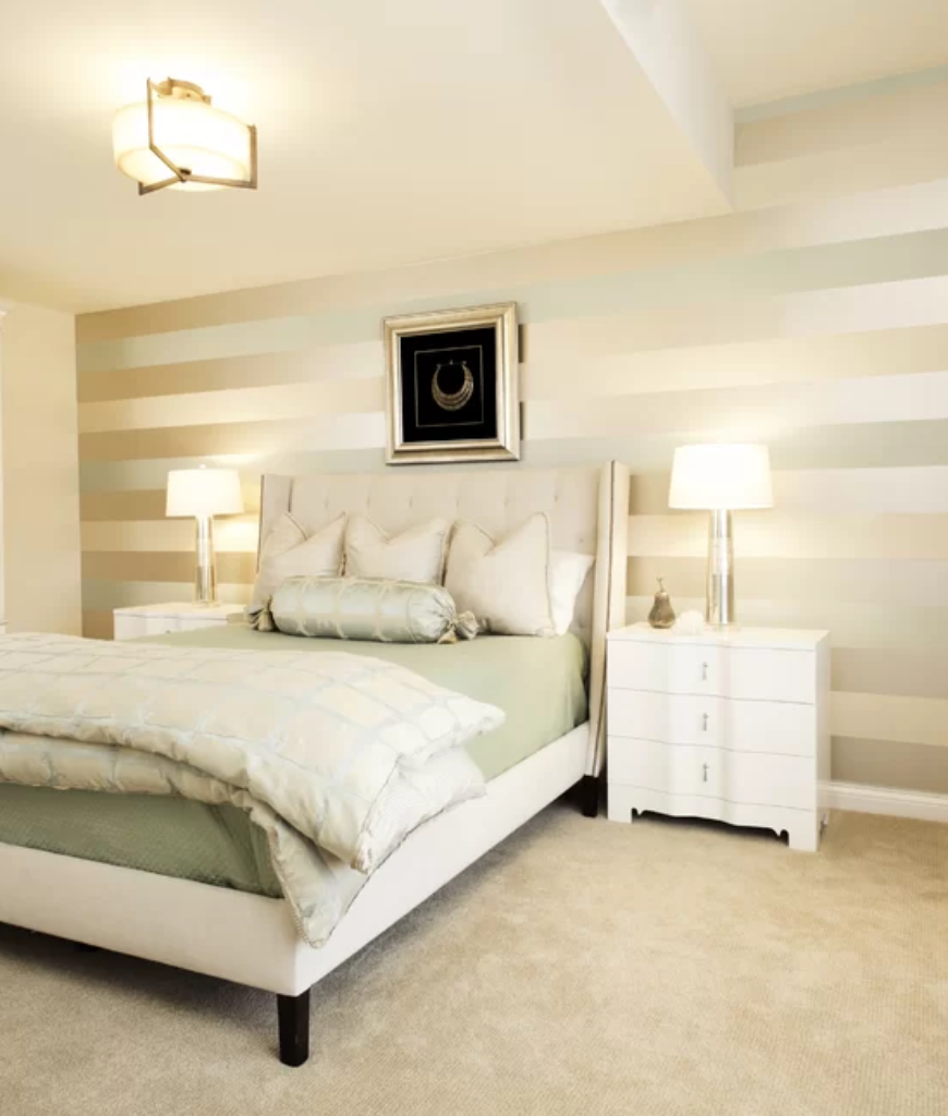 White eclectic bedroom with gray and cream wall pattern design and carpet flooring together with large white bookshelf and table lamps.