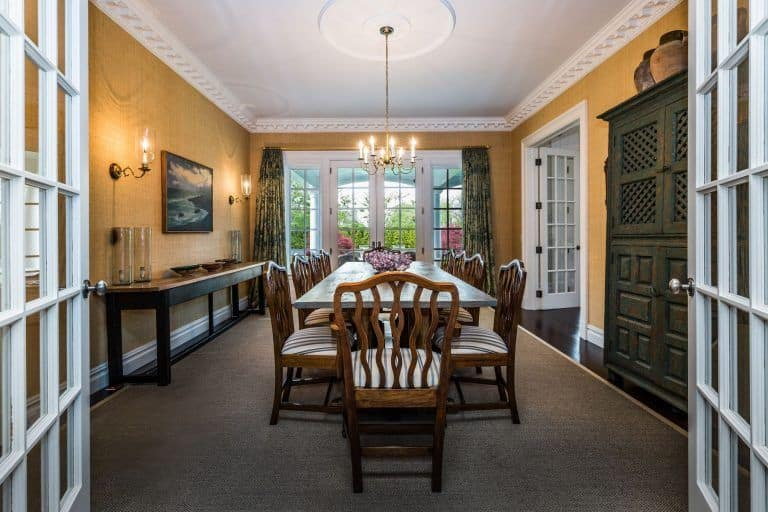 Formal dining room enclosed by French doors boasts a long dining set accompanied by a buffet table. It is lighted by a candle chandelier and matching wall sconces.