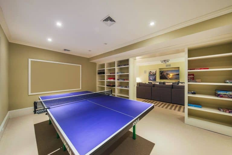 A game room is also present at the mansion lighted by recessed lights. Built-in shelves add style to the room.