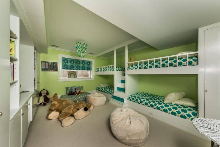 This bedroom can be a guest or kids bedroom. The room features a built-in bunk beds with a carpet flooring. There are multiple built-in shelves for additional storage.