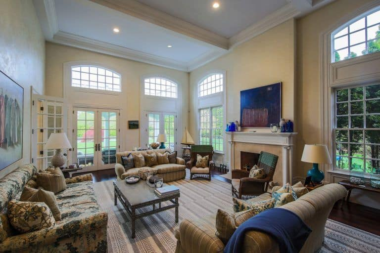 Large living room with a wooden center table surrounded with floral and striped sofas along with wicker chairs that sit in front of the fireplace topped with blue decors and television.
