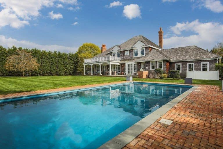 The long rectangular pool mirrors the blue NY sky.