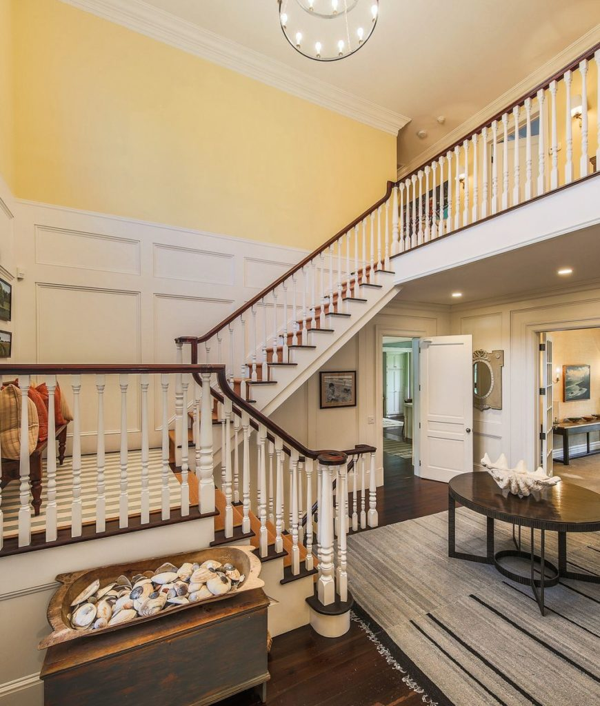 The double height foyer features a traditional staircase lighted by an elegant chandelier.