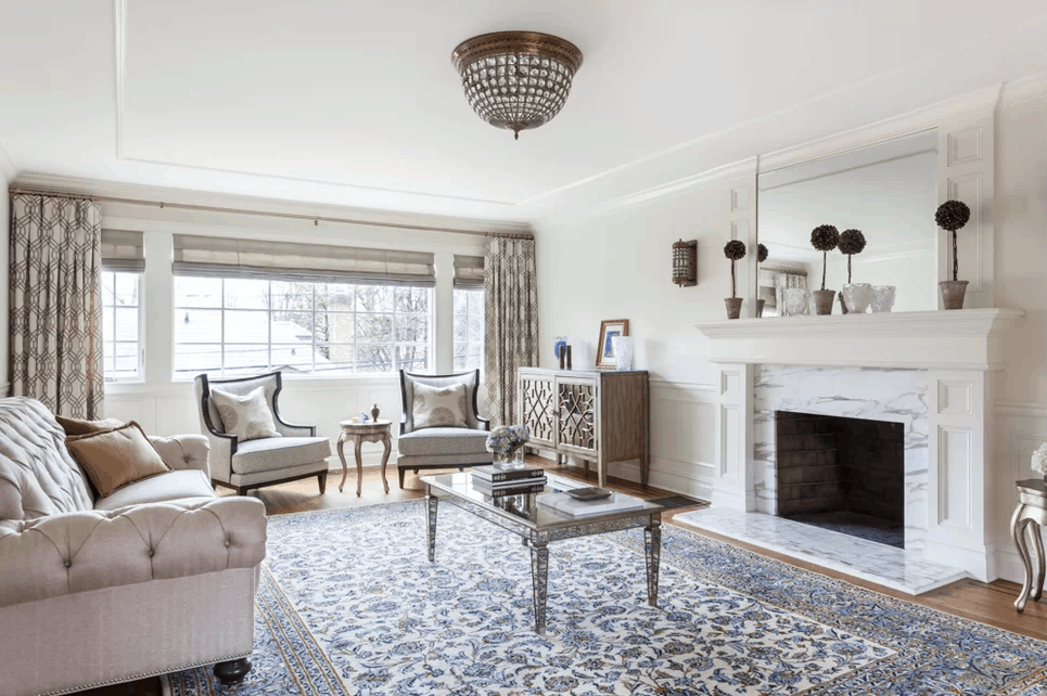 Glam living room with flushmount lighting and a stylish rug along with the fireplace and wide glass window.