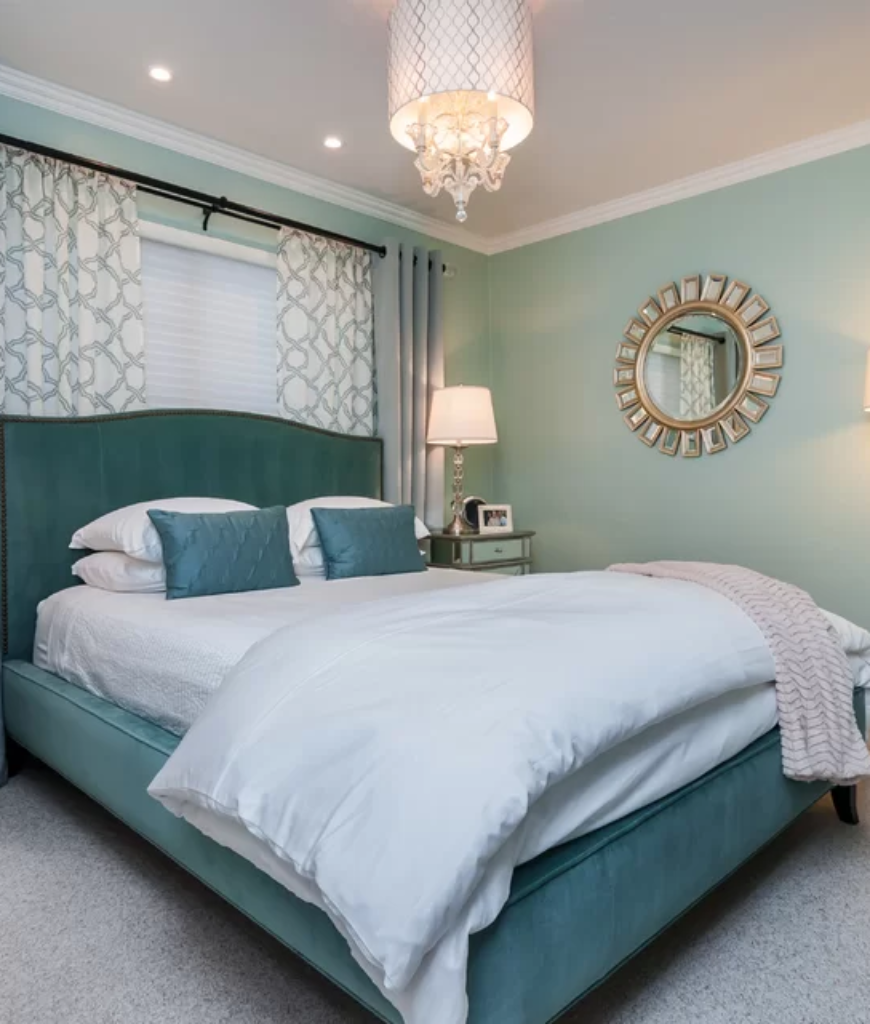 Green glam bedroom with grand chandelier and recessed lights together with carpet flooring and table lamps.