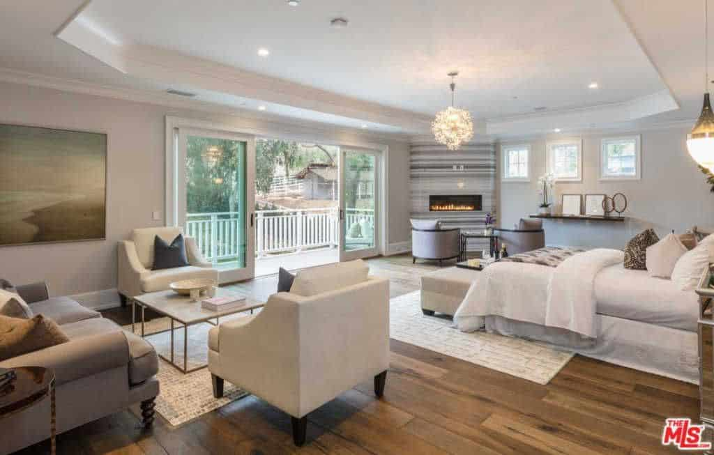 A large traditional primary bedroom offers multiple seating areas and a white bed lighted by a fancy chandelier that hung from the tray ceiling.