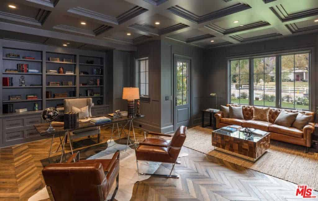 Huge black home office with hardwood flooring and coffered ceiling along with built-in bookshelves and glass windows.