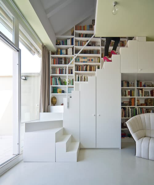 Contemporary white staircase with thin handrail and built-in storage along with bookshelves.