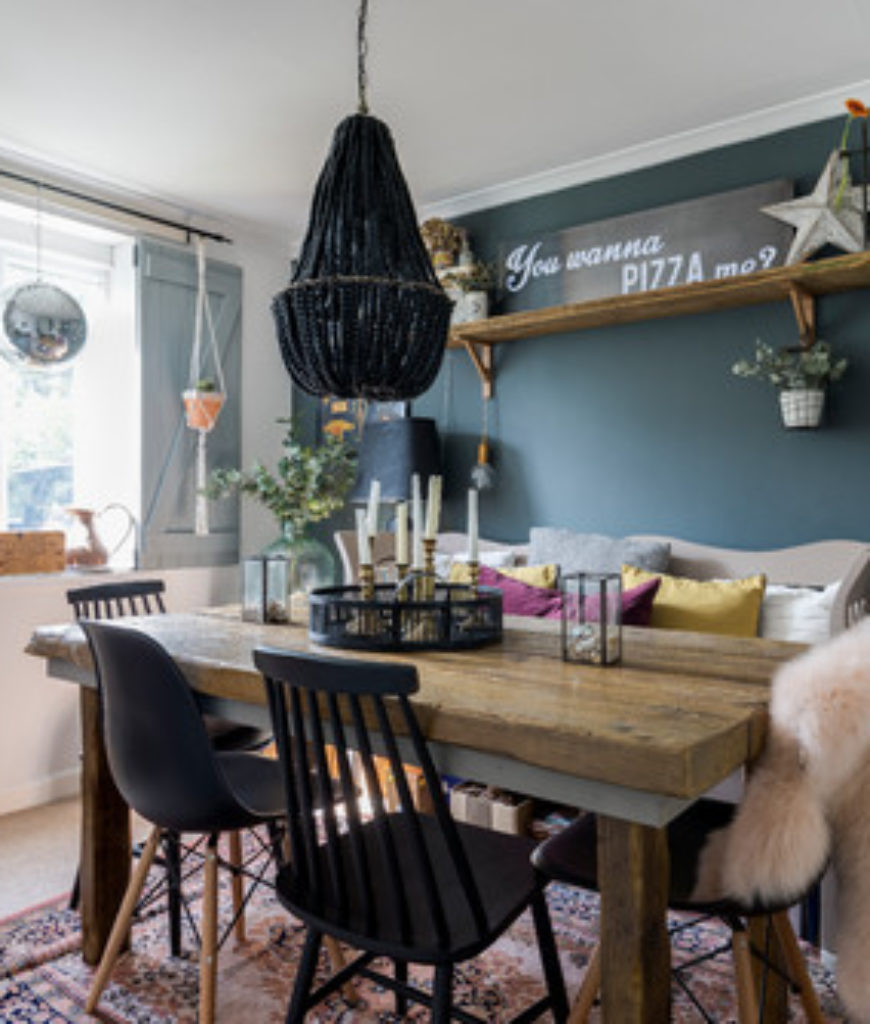 Eclectic dining room with pendant light and black chairs.