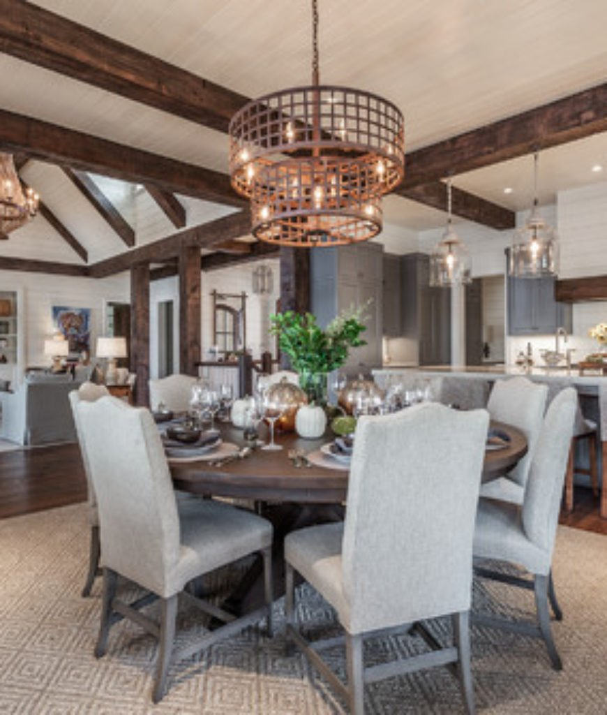 Farmhouse dining room with chandelier and round table.