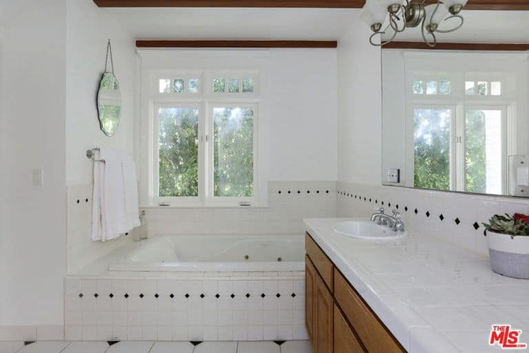 The white bathroom consist of a drop-in tub and a walk-in shower still has a beams ceiling installed along with double sink.