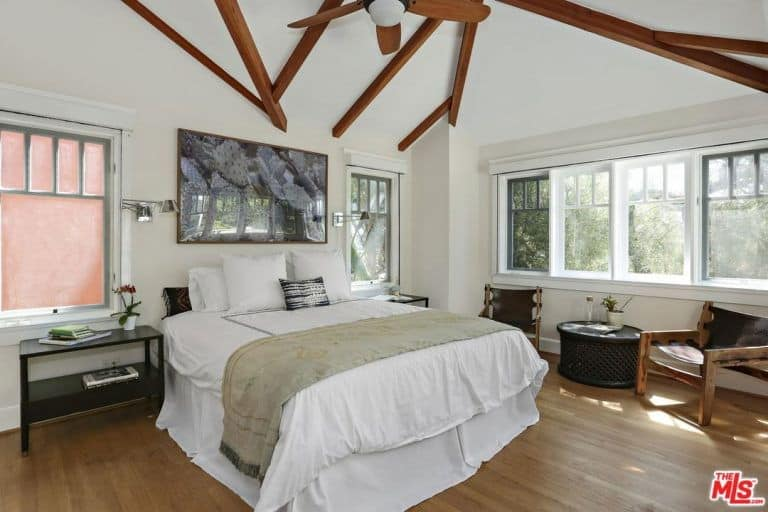 The spacious bedroom features a fireplace and exposed beams along with hardwood flooring that perfectly blends with the white walls.