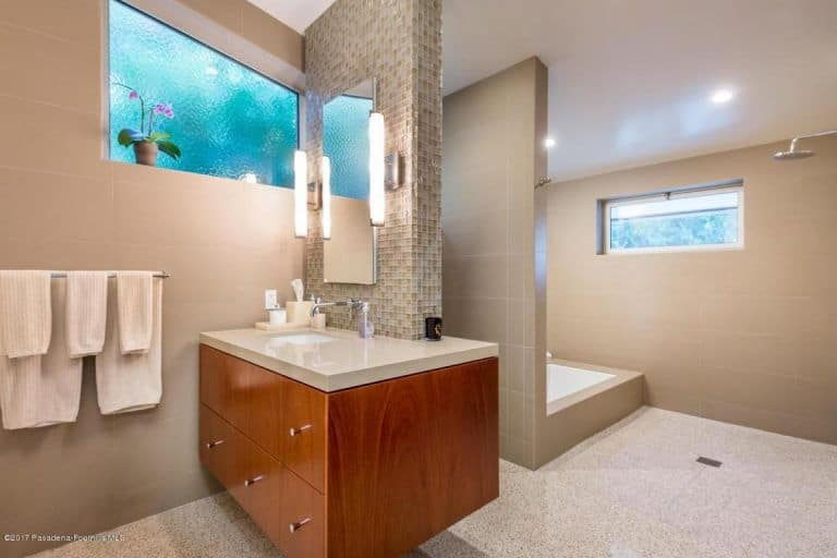 Large mid-century primary bathroom with a floating vanity sink lighted by wall lights, along with a drop in tub and a walk-in shower.