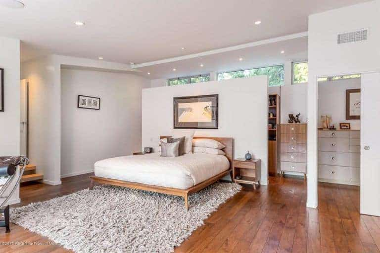 The primary bedroom looks elegant with the scattered recessed lights on the white ceiling. The hardwood flooring blends perfectly with white walls and the rug matches with the bed perfectly.