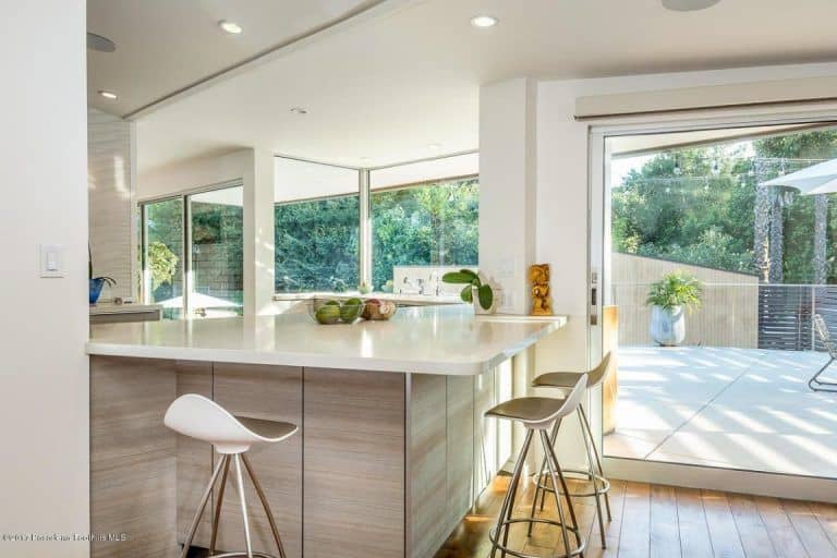 The mansion also boasts a simple but elegant breakfast bar lightened up by the sunlight coming through the glass windows and door. The white counter-tops and stylish kitchen wall add modern taste in the area.