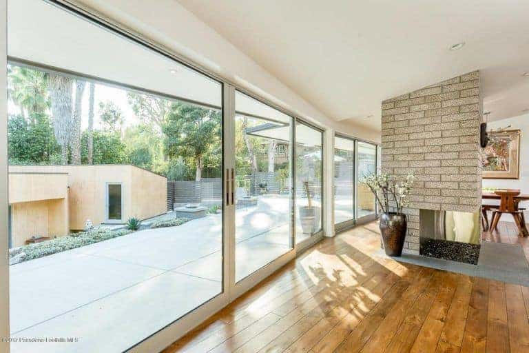The clear glass doors and windows let the sunlight through, that lightens the whole living room area.