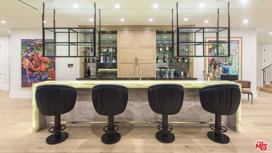 This bar features a stunning counter with stylish bar stools set on the hardwood flooring and lighted by scattered recessed lights.