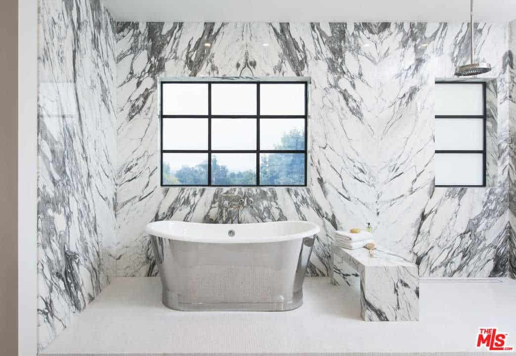 This primary bathroom offers a bench seating made of marble matching the stylish walls. The freestanding tub is set on the white tiles flooring.