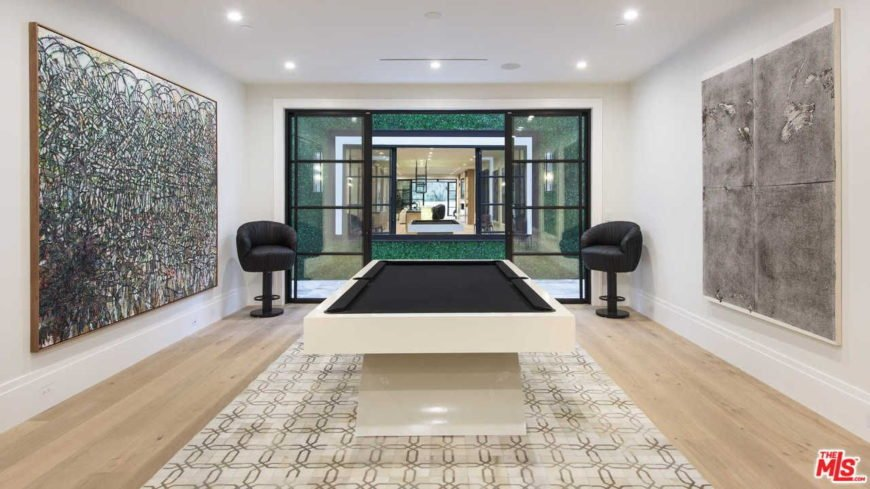 A modish game room featuring a stunning billiards pool and very attractive wall decors.