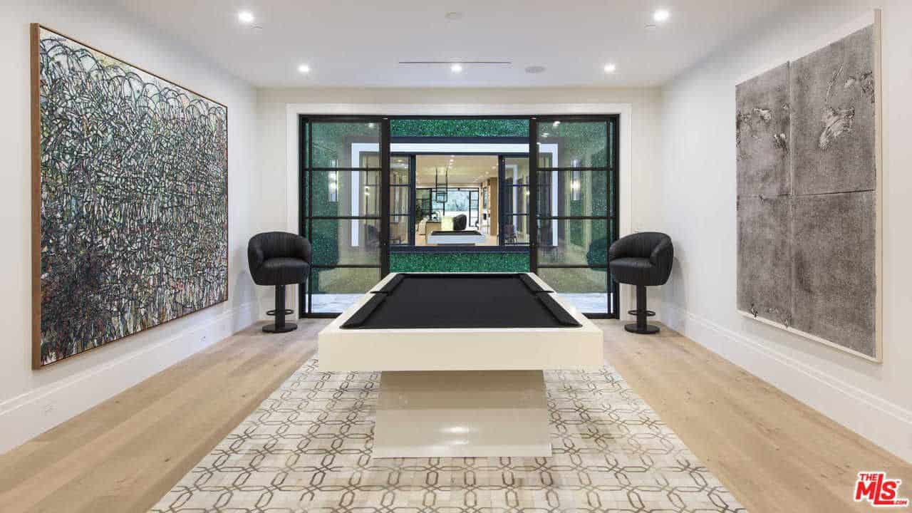 Spacious room designed with huge wall arts mounted on the white wall. There's a pool table on a patterned rug accompanied by black round back stools.