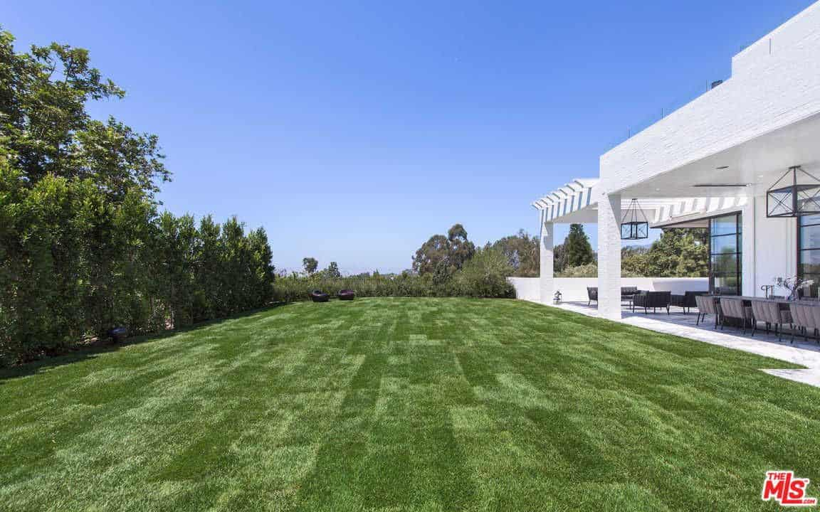 This wide and green garden offers an outdoor kitchen perfect for barbecue under the L.A. sky.