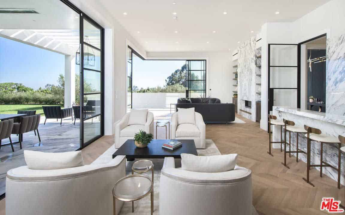 This living room have stunning floor to ceiling glass windows and doors along with multiple recessed lights scattered throughout the ceiling. The white chairs and espresso finished table are perfect on hardwood flooring and rug.