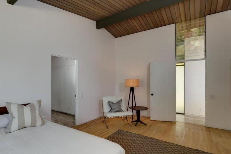This other bedroom is simple, yet offers a peaceful rest with its warm floor lamp perfectly matches the while walls.