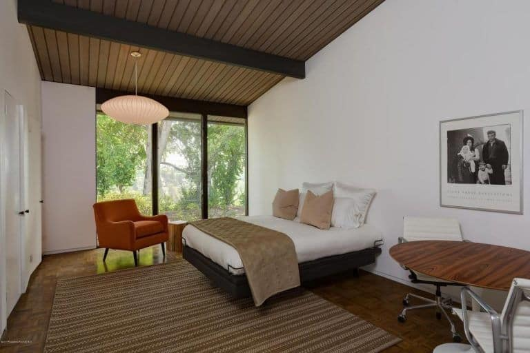 Primary bedroom in a mid-century modern style featuring white walls, hardwood floors and a rustic ceiling with exposed beams.