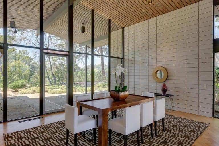 Magnificent dining room with cathedral wood plank ceiling and full height glazing overlooking the outdoor greenery. It has a wooden dining table surrounded with white chairs on a striking brown rug.