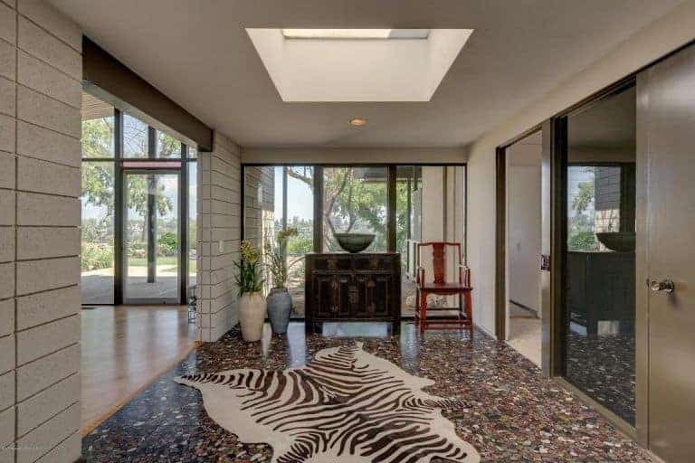 Mid-century style foyer with an elegant-looking flooring lighted by a skylight. The glass windows and doors all fit perfectly with the foyer's style.