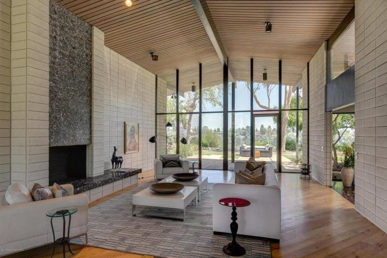Mid-century modern living room with full height glazing and a towering wood plank ceiling mounted with track lights. It has cozy gray seats and a marble fireplace fixed on the white paneled wall.