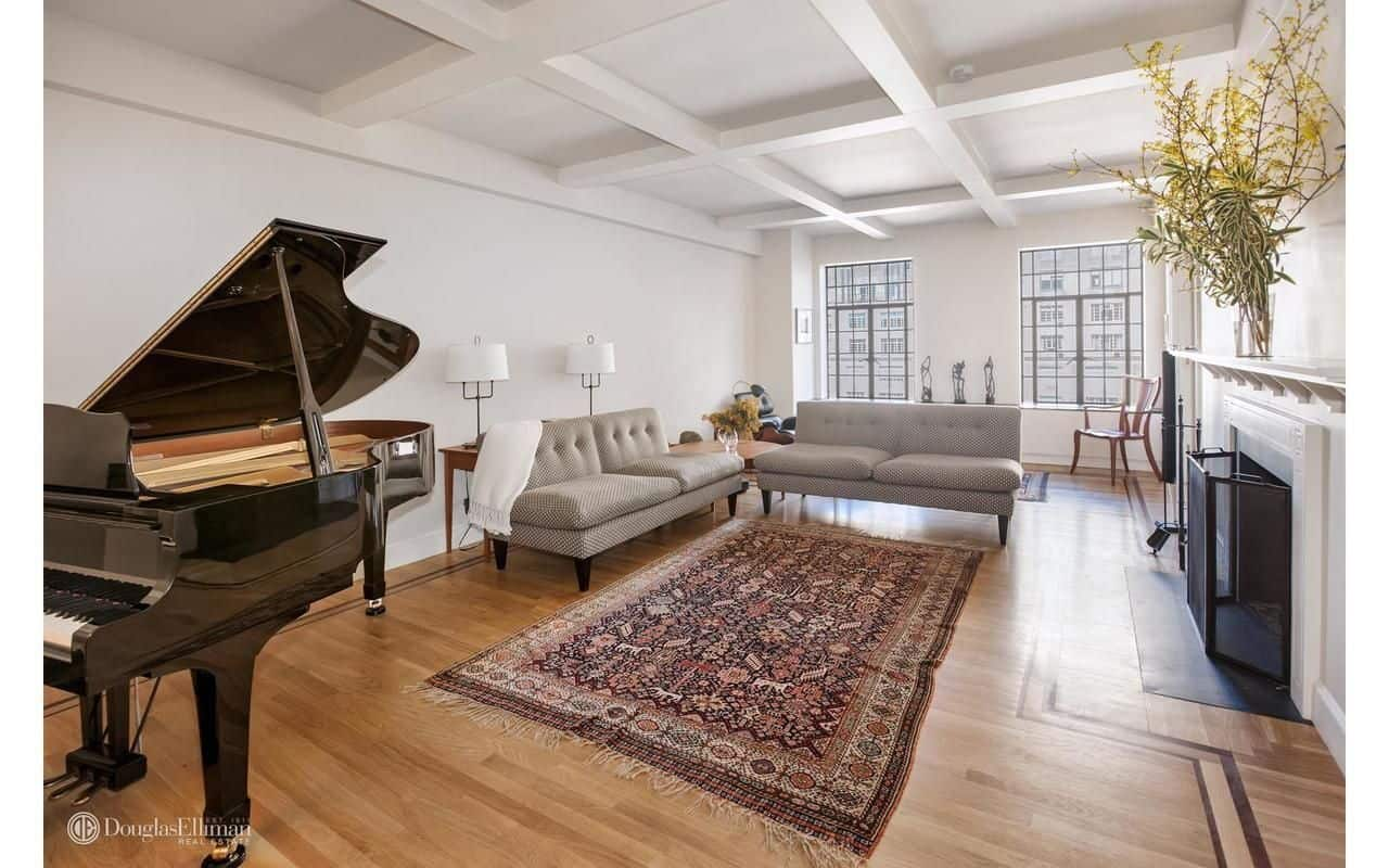 White living room features gray tufted sofas, a baby grand piano and a white fireplace covered with metal fence. It has coffered ceiling and hardwood flooring topped by a vintage rug.